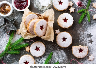 Traditional Christmas Linzer cookies with raspberry jam on dark background.  Austrian biscuits filled. Top view Holiday concept