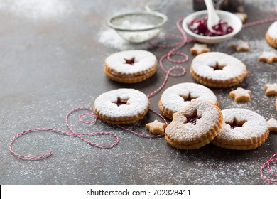 Traditional Christmas Linzer cookies with raspberry jam on dark background.  Austrian biscuits filled. Selective focus Copy space. Holiday concept