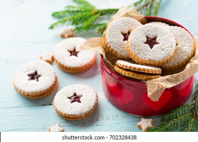 Traditional Christmas Linzer cookies with raspberry jam on blue wooden background.  Austrian biscuits filled. Selective focus. Holiday concept. Homemade sweet present in box