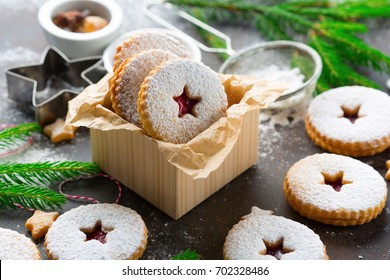 Traditional Christmas Linzer cookies with raspberry jam on dark background.  Austrian biscuits filled. Selective focus. Holiday concept. Homemade sweet present in box