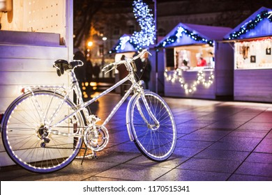 Traditional Christmas market in Europe. Vintage bike with lights decoration on a Christmas fair.