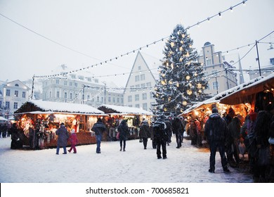 Traditional Christmas market with a Christmas tree, lights, booths and warmly dressed people at the Town Hall square in Tallinn Old Town on a snowy day in Estonia.