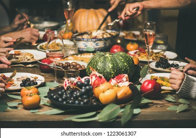 Traditional Christmas or New Year holiday celebration party. Friends or family eating different snacks at Festive Christmas table, selective focus, horizontal composition