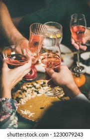 Traditional Christmas or New Year holiday celebration party. Friends or family feasting and clinking glasses with rose wine at festive Christmas table with homemade snacks, vertical composition