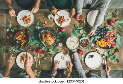 Traditional Christmas, New Year holiday celebration party. Flat-lay of friends or family eating at festive table with turkey or chicken, vegetables, mushroom sauce, fruit, top view