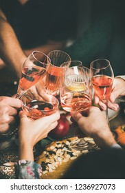 Traditional Christmas or New Year holiday celebration party. Friends or family feasting and clinking glasses with rose wine at festive Christmas table with homemade snacks