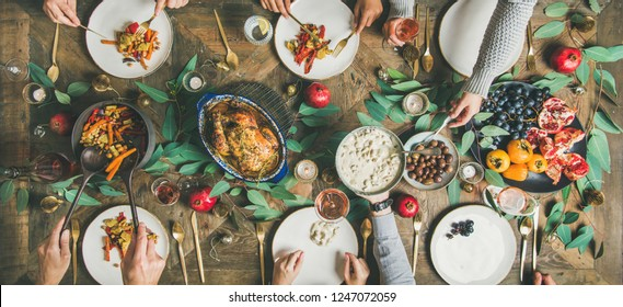 Traditional Christmas, New Year holiday celebration. Flat-lay of friends or family and cat eating at festive table with turkey or chicken, vegetables, mushroom sauce, fruit, top view, wide composition