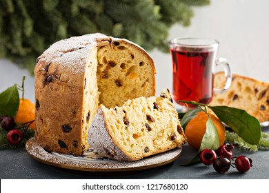 Traditional Christmas panettone with dried fruits and orange zest on light background