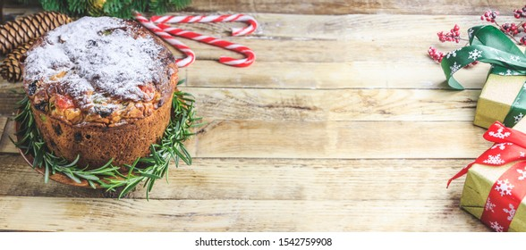 Traditional Christmas panettone with raisins and dried fruits on rustic wooden table. Christmas decorations, caramel canes, cinnamon, star anise, assorted nuts. Selective focus. Web banner