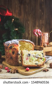 Traditional Christmas panettone with raisins and dried fruits on rustic wooden table. Christmas decorations, caramel canes, cinnamon, star anise, assorted nuts. Selective focus