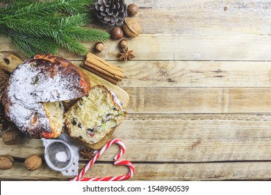 Traditional Christmas panettone with raisins and dried fruits on rustic wooden table. Christmas decorations, caramel canes, cinnamon, star anise, assorted nuts. Top view. Flat lay. Selective focus