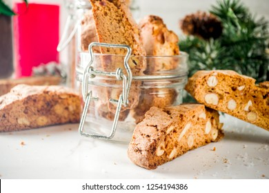 Traditional Christmas pastries, Italian homemade double-baked biscotti or cantuccini cake, with nuts and dried fruits. with xmas decorations and fir branches, white marble background copy space