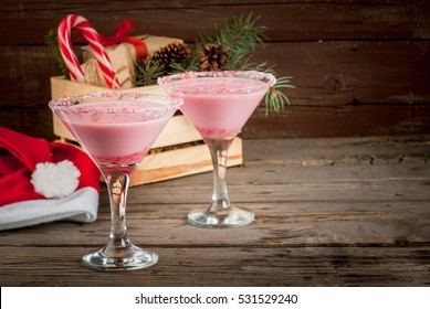 Traditional Christmas pink cocktail candy cane punch in glasses, decorated with shards of candy cane. Against box with gifts, the Christmas tree branches and decorations, copy space, selective focus