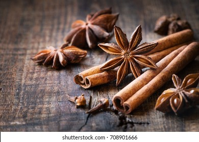 Traditional Christmas spices - Star anise with cinnamon and cloves on dark rustic wooden background