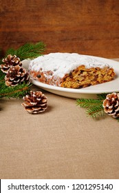 traditional Christmas Stollen on plate, wooden background