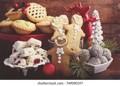 Traditional Christmas sweets and party food. spotlighted in festive setting with rustic style gifts and decorations on dark vintage wood background with applied retro style filters.