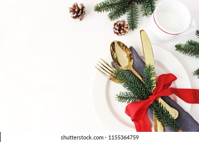 Traditional Christmas table place setting. Golden cutlery, linen napkin, spruce branches and cup of milk. Pine cone and red ribbon decoration. Holidays background. Flat lay, top view with copy space.