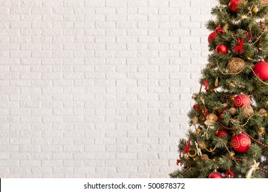 Traditional Christmas tree on a white brick wall background
