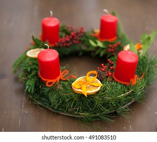 Traditional christmas wreath made with spruce branches, candles and slices of citrus on the old table
