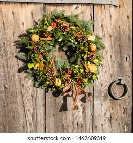 A traditional Christmas wreath on an Elizabethan (16C) oak entrance door (close up)