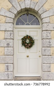 Traditional Christmas wreath on an English country house door. Suitable for a Christmas card or magazine cover.