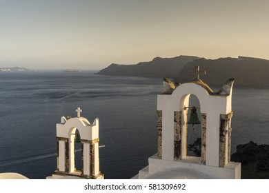 Traditional church belfry at sunset in Oia, Santorini, Greece