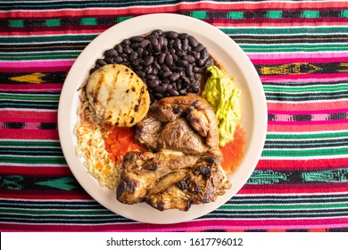Traditional churrasco plate served in Guatemala. Lunch consists of grilled meat, beans, rice, potato, salsa, and guacamole.