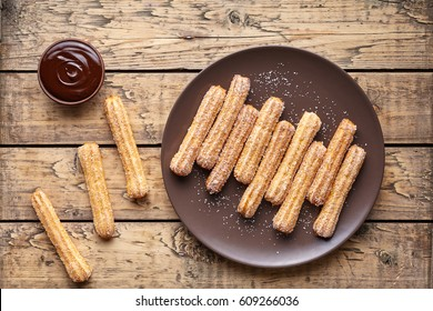 Traditional churros Spanish homemade sweet dessert pastry food on vintage wooden table background