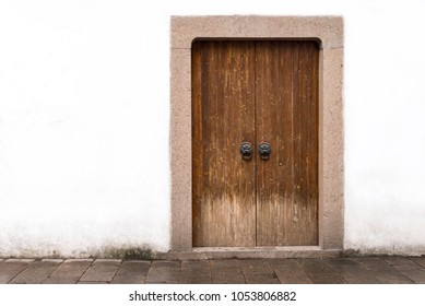 Traditional classic chinese wood door or gate with locked key and bronze lion head knob and white stone wall in ancient chinese house, china