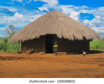 Traditional clay house with straw roof and straw. The African village is traditionally made of clay and clay house, opposite boy. Jinja-Uganda, Africa 17 june 2016