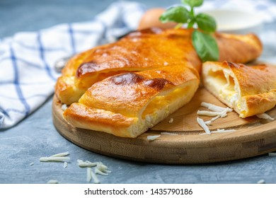 Traditional closed pie with cheese and egg in the shape of a crescent cut into pieces on a wooden serving board, selective focus.