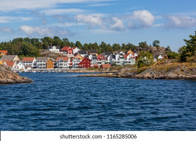The traditional coastal wooden houses covered in sunlight in the Lyngor archipelago, Southern Norway