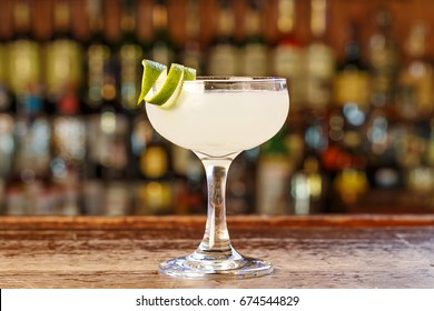 Traditional cocktail daiquiri, image for the menu. decorated with lime at bar background. Background blurred with soft focus. Space for text
