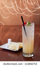 traditional cocktail on a bar top with sugar cubes and lemon slices on the side, tom collins or vodka collins