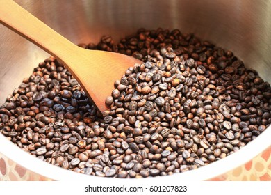 Traditional coffee beans roasting in metal basin with spatula as background or print card.