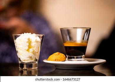 Traditioneller Kaffee aus Triest Italien. Schwarzer Espresso im Glas, mit Creme und Makaroon.