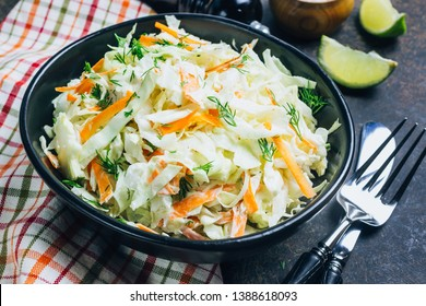 Traditional cole slaw salad in a black bowl. Fresh cabbage and carrot salad with mayonnaise. Dark background. Selective focus