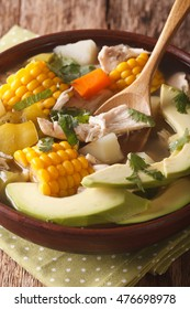 Traditional Colombian ajiaco soup close up in a bowl on the table. vertical
