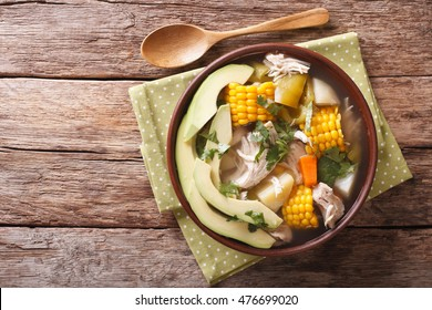 Traditional Colombian ajiaco soup close up in a bowl on the table. horizontal view from above