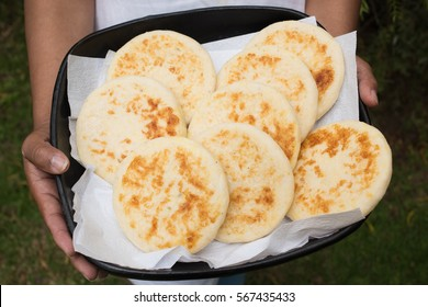 traditional colombian arepas - regional food in a try woman hands holding an try