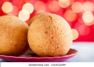 Traditional Colombian bunuelos (Deep Fried Cheese Bread) on christmas red background