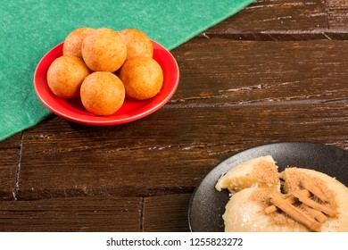 Traditional Colombian bunuelos (Deep Fried Cheese Bread) and natilla on christmas. Wood background