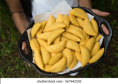 traditional colombian empanadas - regional food in a try woman hands holding an try
