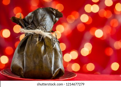 Traditional Colombian tamale as made on Tolima region over a christmas red background
