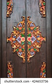 Traditional colorful Balinese style carved door, made of wood, in Ubud, Bali, Indonesia.