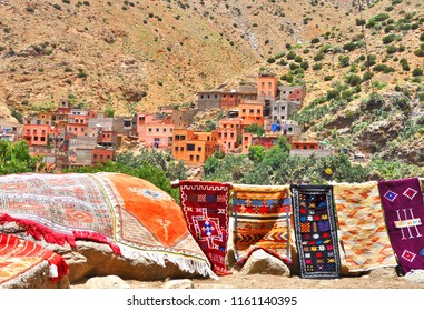 Traditional colorful Berber Village in Atlas Mountains, near Marrakesh, Morocco. Woven carpets made using  traditional Arab carpet-making techniques in the foreground.