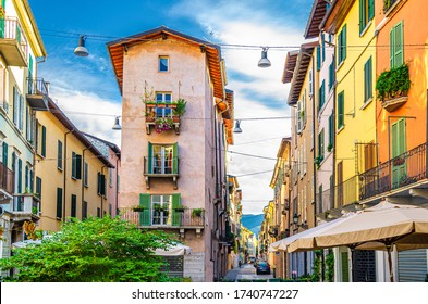 Traditional colorful building with balconies, shutter windows and multicolored walls in typical italian street, Brescia city historical centre, blue sky background, Lombardy, Northern Italy