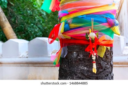 The traditional colorful fabrics tied on the tree in the Thai Buddhist Temple for praying with a mini flower garland and white lotus
