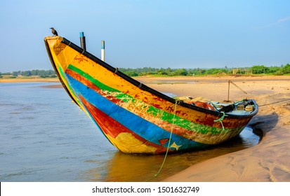 """Traditional colorful fishing boat anchored at the confluence of Mahendra Tanaya river and Bay of Bengal, copy space. On the boat it's written """"May the Ocean God be kind"""", non copyrighted design."""
