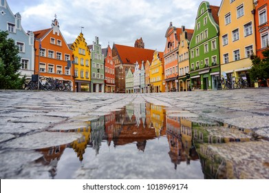 Traditional colorful gothic houses in the Old Town of Landshut, historical town in Bavaria by Munich, Germany, reflecting in a rain puddle
